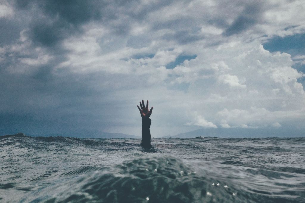 Hand coming up from the water portraying how startups can start to sink if they don't scale sustainably.