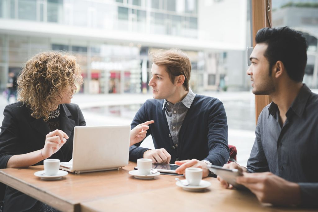 Small business owner consulting with a team of experts at a coffee shop