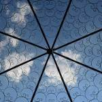 Looking up through a metal grill work at the blue sky above. There are spokes in the grill work, with concentric rings encircling the center of the spokes, and white clouds can be seen in the sky above.