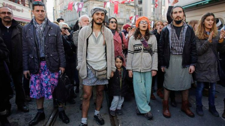 Men, wearing skirts, march during a protest against domestic violence, in central Istanbul
