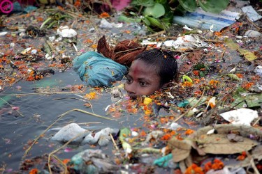 Boy Swimming In Polluted Water