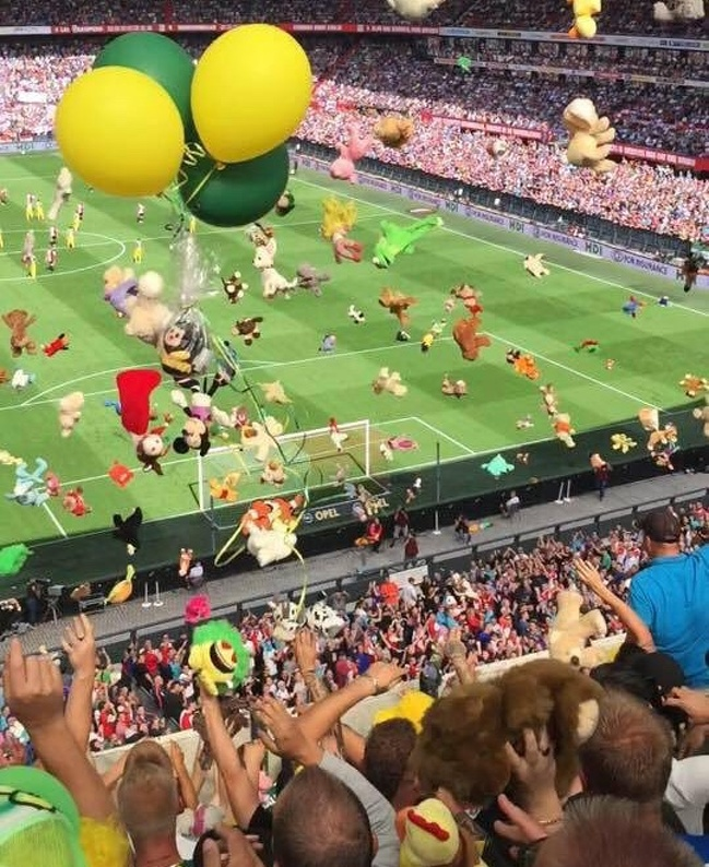 23. Fans are throwing toys at the stand where there are little patients from a local hospital.