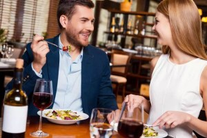 Enjoying meal together. Beautiful young loving couple enjoying dinner at the restaurant
