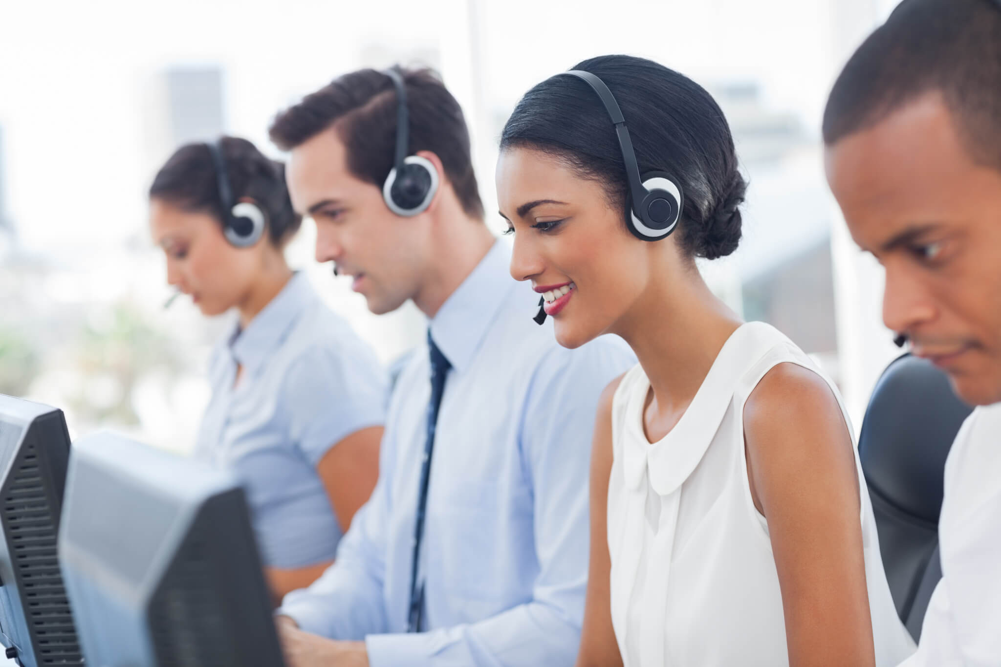 Smiling call center employees sitting in line with their headset