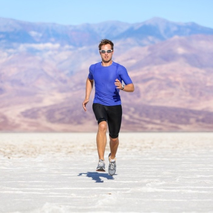 Running man - sprinting athlete runner in desert. Fit athletic male fitness model in fast sprint run at great speed towards camera. Sport in amazing extreme desert landscape.