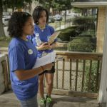 2 young women standing on a porch with clipboards waiting to talk to a voter