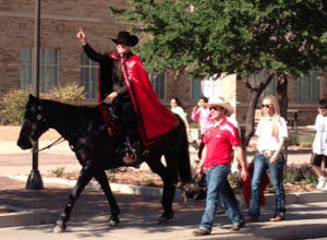 The Masked Rider throwing up his guns during the March of Dimes. Photo by Jodie May