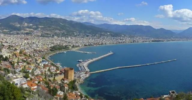 Das türkisblaue Meer der Türkischen Riviera mit dem Hafen von Alanya und dem Wahrzeichen der Stadt, dem Roten Turm.