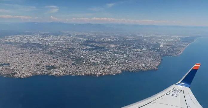 Antalya, Kaleici und der Flughafen von Antalya aus einem Flugzeugfenster aus aufgenommen. Mit den Klippen am Meer, einem Teil des Flügels und den Landebahnen des Flughafens.