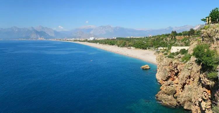 Der Blick von den Klippen am Konyaalti Strand auf den Strand und das dahinterliegende Taurusgbirge.