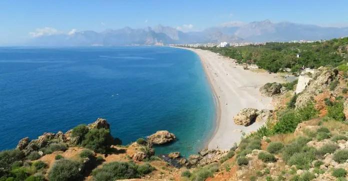 ein sicherlförmiger, kilometerlanger Sandstrand. Im Vordergrund sind Klippen am einenen Ende zu sehen und weit im Hintergrund die Berge des Taurusgebirges. Rechts am Strand gibt es einen grünen Park und es sind die Häuser in Antalyas Stadtteil Konyaalti zu sehen.