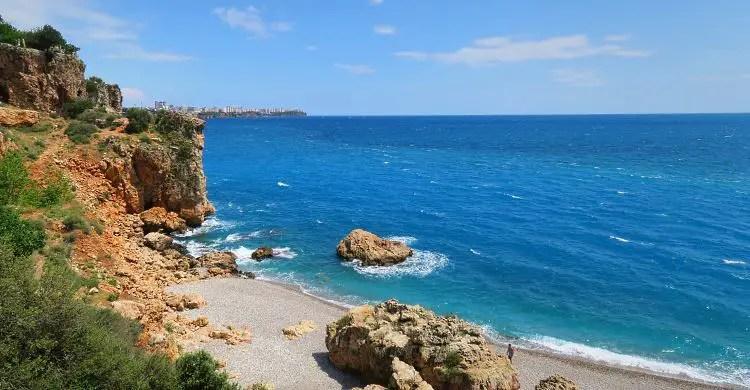 Der Ostende des Konyaalti Strand an den Klippen der Altstadt Kaleici mit dem Blick auf das türkisblaue Meer hinaus.