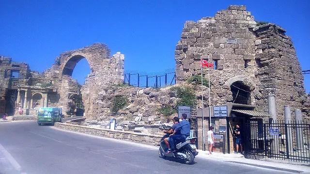 Ruinen des Stadttores von Side. Unter dem Torbogen führt eine einspurige Straße hindurch