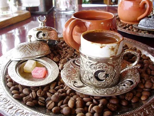 Eine Tasse Kaffee steht auf einem Teller auf dem Kaffeebohnen liegen.