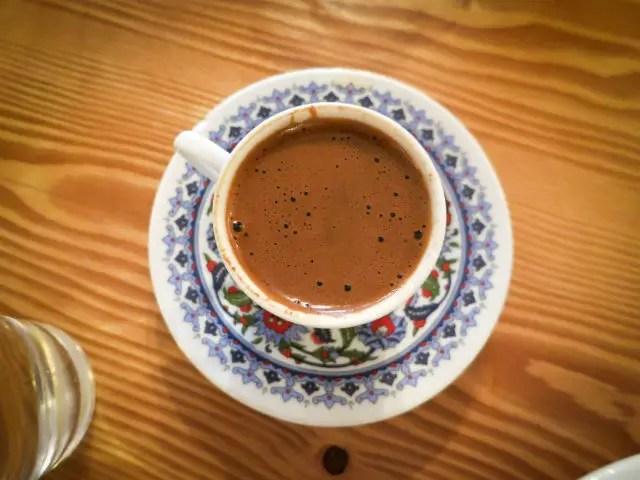 Eine mit ornamenten verzierte Tasse die mit türkischem Kaffee gefüllt ist. Sie ist von oben fotografiert sodass man den Schaum gut sehen kann.