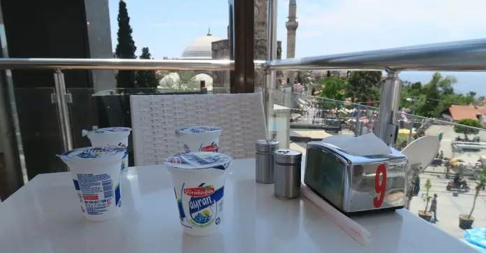 Vier Ayran Becher stehen auf einm Restauranttisch. Dahinter ist das Meer zu sehen und eine Moschee.