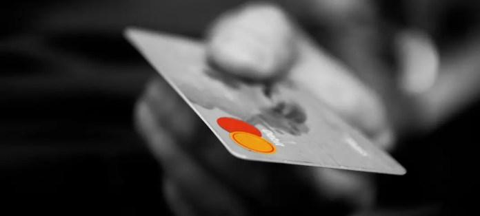 Schwarz-Weiß Foto einer Kreditkarte. Die Karte wird gerade dem gegenüber zum Bezahlen gereicht.