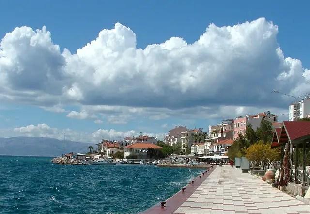 Hafenpromenade von Cesme in der Türkei. Am Himmel sind ein paar Wolken zu sehen. Am linken Bildrand ist das türkisblaue Wasser des Ägäis zu sehen.