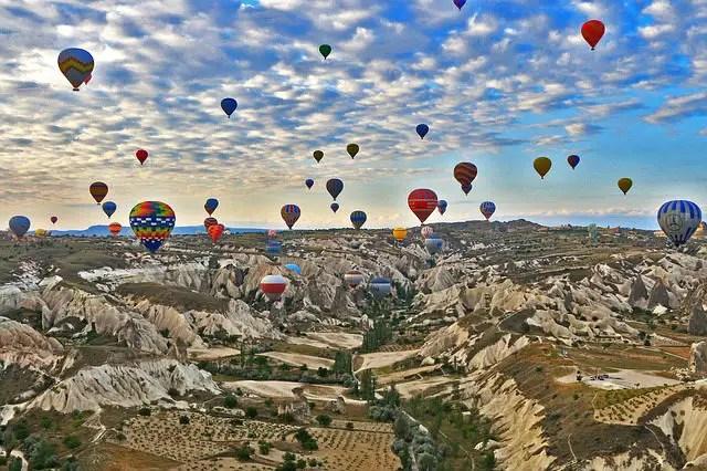 Dutzende Heißlufballone schweben über das kargen Landschaft Kappadokiens. Der Untergrund ist spärlich bewachsen. Die bunten Ballone heben sich deutlich von der braun-grünen Landschaft ab.