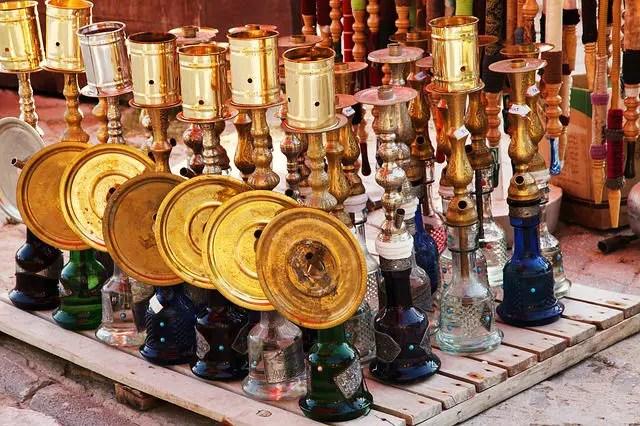 mehr als 10 Nargile (Wasserpfeifen) mit einem in verschiedenen Farben gefärbten Glasbehälter und Kronen für die Asche aus Kupfer