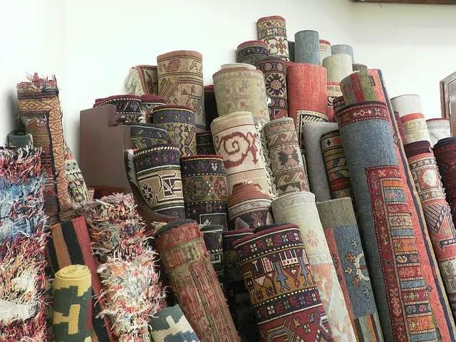 Viele aufgerollte türkische Teppiche stehen an eine Wand gelehnt.