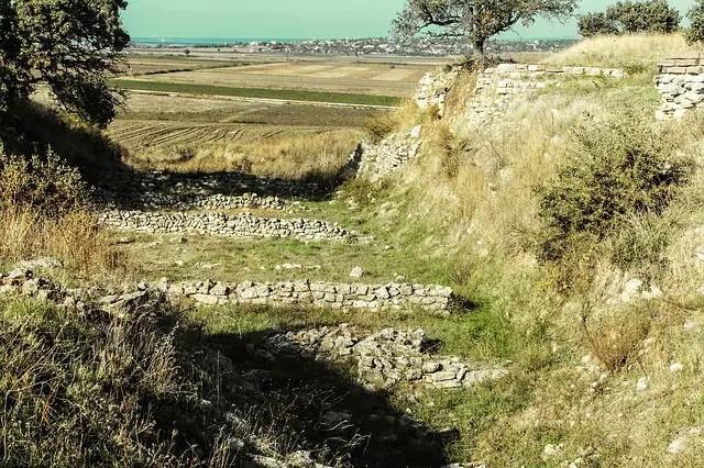 Der von Schliemann in den Hügel von Troja gegrabene Graben. Darin sind Mauerreste zu sehen. Der Blick geht Richtung Meer hinaus.