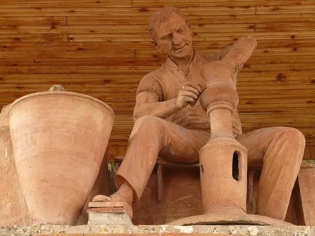 Eine aus Ton gebrannte Statue eines Töpfers. Er dreht gerade einen neuen Krug. Daneben steht ein großer Tonkrug.