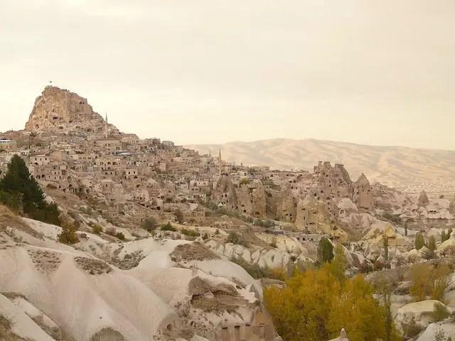 Die in Sandstein gehauenen Häuser und die Festung Uchisar in Kappadokien. Die Landschaft ist spärlich bewachsen. Die Gebäude sind in den Stein gehauen worden, wie Hölen.