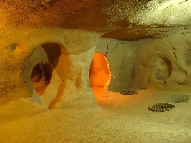 Gang in einer unterirdischen Höhlenstadt in Kappadokien. Sie ist mit elektrischen Licht beleuchtet.