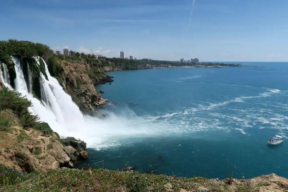 Ein Ausflugsboot ist neben dem Wasserfall zu sehen. Es zeigt deutlich die Größenverhältnisse zwischen dem 40 Meter hohen Wasserfall und den sich darauf befindlichen Menschen