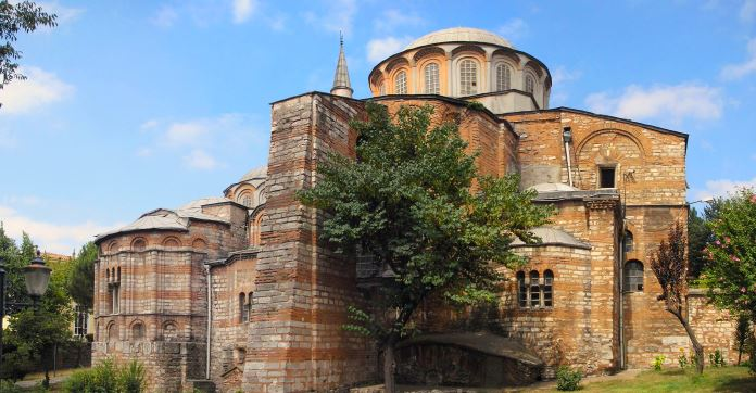 Aus Steinen erbaute Chora Kirche an einem sonnigen Tag. Davor ist ein kleiner Baum zu sehen.