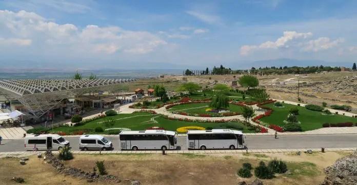 Blick von einem 10 Meter hohen Hügel auf den Eingangsbereich der Ruinen von Hierapolis. Auf einem Parkplatz stehen mehrere weiße Busse. Zwischen den alten Stadtmauern und den Bussen ist ein grüner Park mit vielen bunten Blumen zu sehen