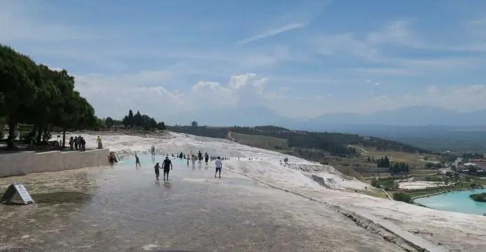 Blick von der oberen Seite der Kalkterrassen in Pamukkale auf das hinunterfließende Thermalwasser und die darin Badenden Menschen