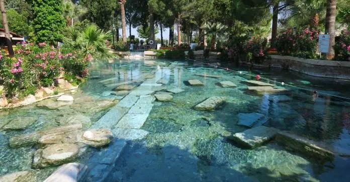 Das türkisblaue, durchsichtige Wasser im Kleopatra Pool. Im Pool sind Mauerreste und Säulen den Ruinen von Hierapolis zu sehen.