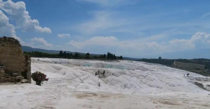 Panoramablick auf die Kalkterrassen von Pamukkale. Blick auf die mit Thermalwasser befüllten Kalkbecken und eine auf der rechten Seite des Bildes zu sehende Mauer.