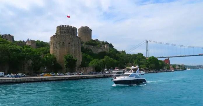 Die in den Hang gebaute Rumelianische Festung mit ihren großen Türmen am Bosporus. Am Wasser fährt ein Schiff-Dahinter ist die zweite Bosporus Brücke zu sehen.
