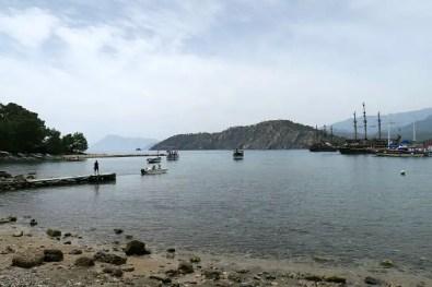 Ausflugsschiffe im Piratenlook im alten westlichen Hafen von Phaselis. Am Strand sind Badegäste zu sehen. Im Hintergrund sind Berge und Wälder zu sehen.