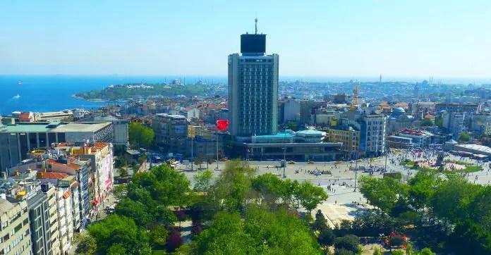 Blick auf den Taksim Platz und ein Hochaus neben dem Platz. Davor ist ein grüner Park zu sehen. Dahinter ist in einiger Entfernung der Bosporus, das Marmarameer und der Stadtteil Sultanahmet zu sehen.