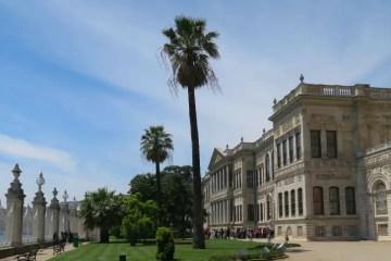 Park des Dolmabahce Palast. Auf der rechten Seite des Bildes hängt eine große Türkische Flagge am Palast. In der Bildmitte ist eine Palme und der grüne Rasen des Parks. Auf der linken Bildseite ist der weiße Zaun zum Bosporus.