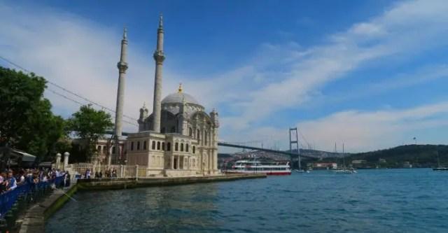 Blick auf die weiße Ortaköy Moschee mit zwei Minaretten, sie steht direkt m Bosporusufer. Dahinter führt die Bosporusbrücke (Hängebrücke) auf die andere Seite des Bosporus.