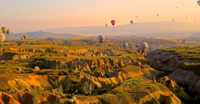 Die zerklüftete Landschaft in Kappadokien mit ihren sandsteinfarbenen Schluchten, kärglich grünen Gras, Bergen und dutzenden Heißluftballonen in der Luft.