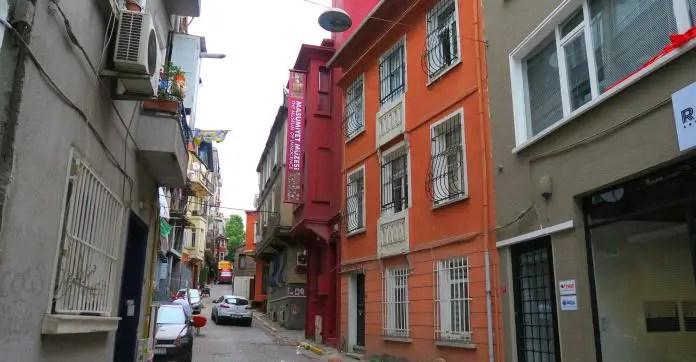 """Dunkelrotes Gebäude in einer schmalen Straße mit einem Schild auf dem """"Museum of Innocence"""" steht."""