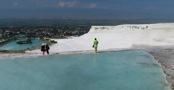 Blick vom oberen Rand der Wasserbecken auf die Kalkterrassen von Pamukkale, das türkisblaue Wasser darin, die schneeweißen Kalkablagerungen und den See darunter.