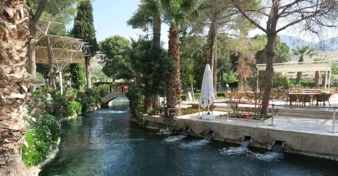 Ein schmaler Teil des Pool mit einem Gastgarten daneben. Am Rand des Pools ist das zufließende Thermalswasser zu sehen.