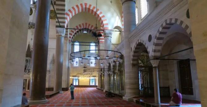 Männer beten. Die kupel- und torartigen Elemente der Moschee mit ihren roten Verzierungen.