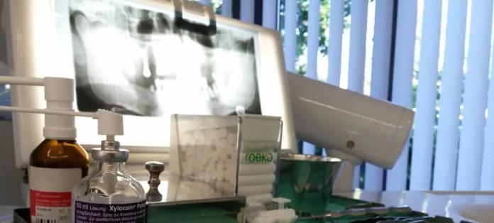 Röntgen Aufnahme eines Zahnarztes in der Türkei. Blickwinkel von einem Behandlungsstuhl. Davor liegt eine Karte einer Auslandskrankenversicherung.