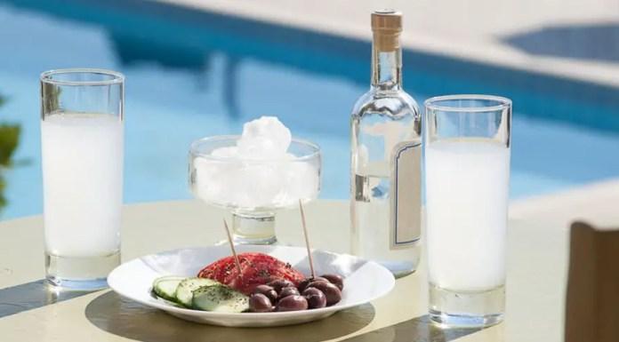 Raki in einer Flasche und in zwei Gläsern auf einem Tisch vor einem Pool