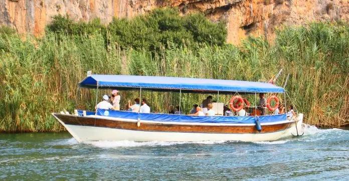Ein blau-weiß-braunes Boot fährt mit einigen Touristen am Dalyan Fluss zum Strand.