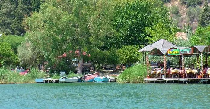 Ein überdachtes Restaurant am Dalyan Fluss im Sommer. Es hat keine Wände. Darin sind viele Touristen zu sehen.