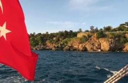 Die türkische Flagge hängt am Heck eines Bootes an einem Feiertag in der Türkei. Aufgenommen vor den Klippen von Antalya.